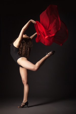 Modern style dancer with red fabric posing on a studio grey background Standard-Bild