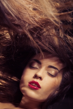 A beauty shot of a young woman with red lips and flowing hair over dark background photo