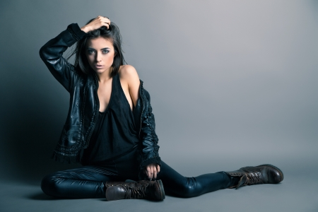 Fashion model wearing leather pants and jacket posing on grey background Stock Photo