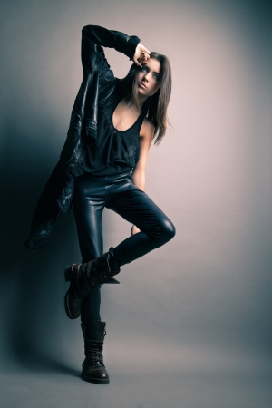 Fashion model wearing leather pants and jacket posing on grey background Stock fotó