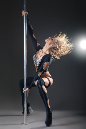Attractive sexy woman pole dancer performing against grey background photo