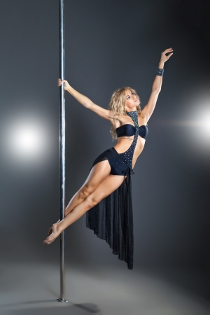 Young sexy woman exercise pole dance against a dark background