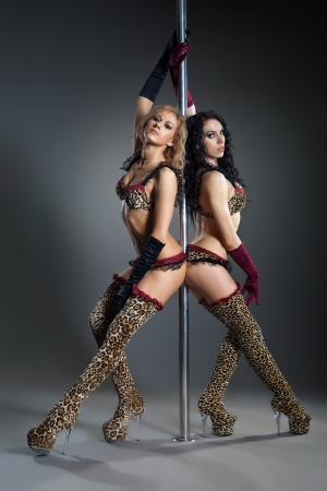Two young sexy women exercise pole dance against a dark background