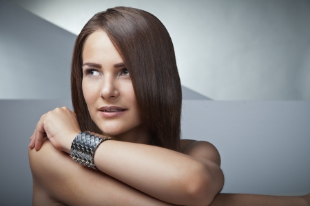 Beautiful woman with long brown straight hairs on grey background photo