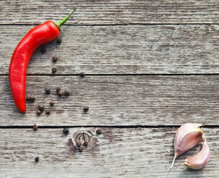 Red hot chili peppers with garlic on wooden background
