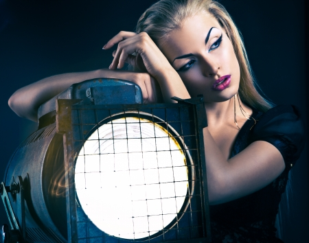 Sexy young woman with old floodlight over dark background Standard-Bild