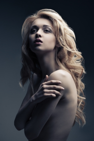 Portrait of beautiful posing blond woman with long curly hair on black background