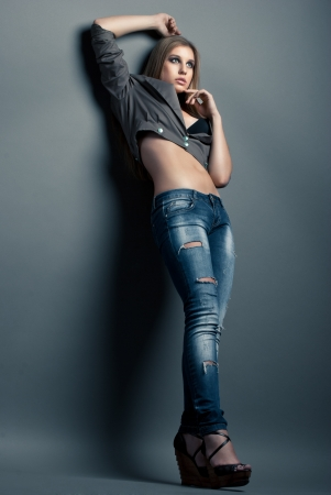 Fashion photo of young sensual woman in jeans over grey background photo