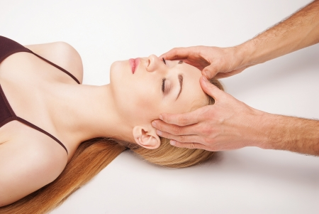 Young bright woman receiving a head massage in a spa centre photo