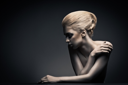 high fashion: Beautiful high fashion female model with abstract hair style behind the table