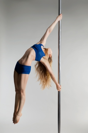 Young slim pole dance woman exercising over light grey bacground photo