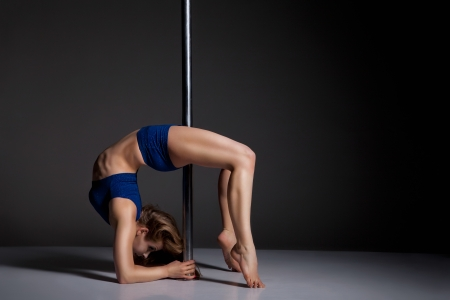 nude gymnast: Young slim pole dance woman exercising over dark background