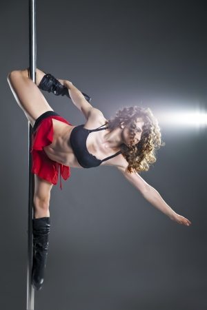 Young slim pole dance woman exercising over dark background photo