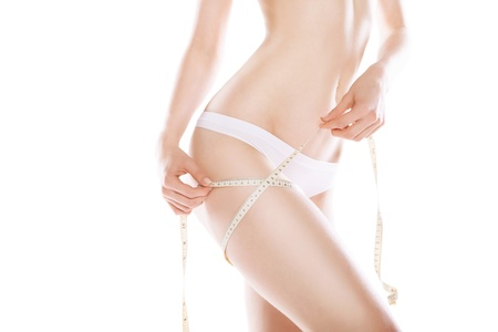 slimming woman measuring her thigh with measuring tape over white background