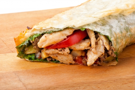 chicken burrito with fried potato and tomato on plate photo