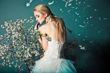 esküvő: Portré egy nő az esküvői ruha mögött ágak virággal