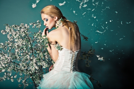 Portrait of a woman in wedding dress behind the branches with flowers photo