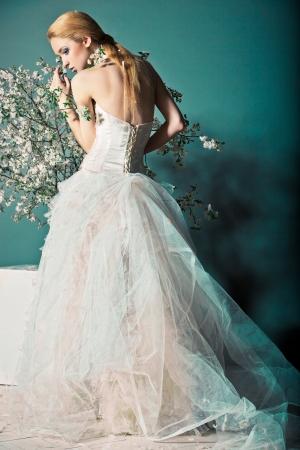 花と枝の背後にある結婚式のドレスを着た女性の肖像画 写真素材