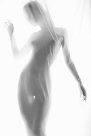 The body of a beautiful naked woman through the transparent fabric on a light background