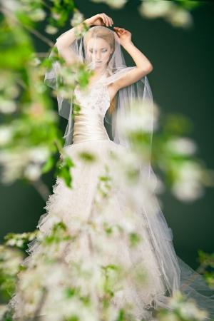 Retrato de una mujer en traje de novia detrás de las ramas verdes con flores