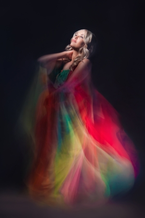 Young beautiful female model in colorful dress on black background photo