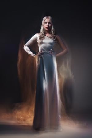 Belle jeune modèle féminin en robe blanche sur fond noir