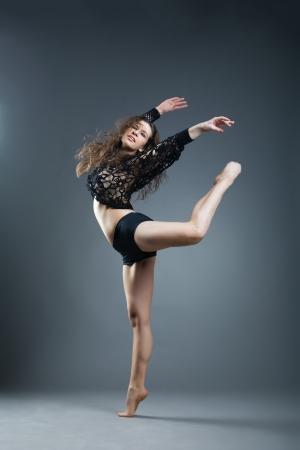 Modern style dancer posing on a studio grey background photo