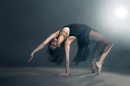 danza contemporanea: Bailar?moderno del estilo que presenta en un estudio de fondo gris en la niebla
