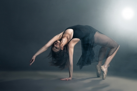 contemporary: Modern style dancer posing on a studio grey background in fog Stock Photo