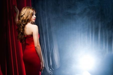 무대 앞의 빨간 드레스를 입고 포즈 아름 다운 여자의 초상화