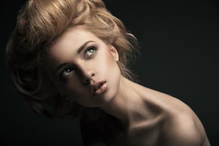 Mooie high fashion vrouwelijk model met abstracte kapsel achter de tafel Stockfoto