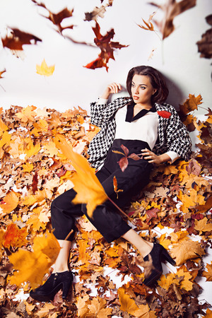 Young brunette woman portrait in lying autumn leaves photo