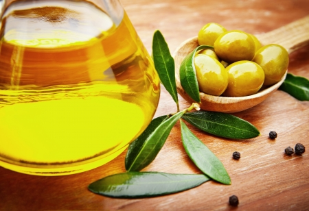 oilcan: Extra virgin healthy Olive oil with fresh olives on rustic wooden background Stock Photo