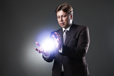 Hand of Business Man Hold light on dark background photo