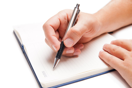 Man hand writing in open book isolated on white background Standard-Bild