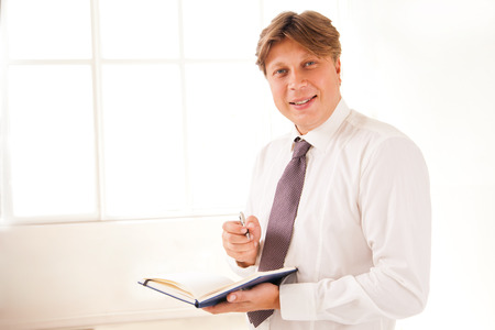 Smiling Businessman standing in office holding diary on white photo