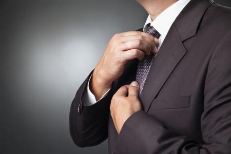 portret van de mooie zakenman in zwart kostuum binden iemands stropdas Stockfoto