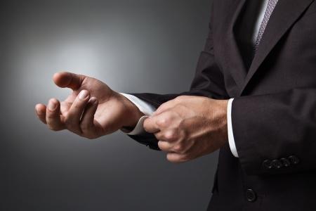 Close-up van elegantie man handen met manchetknoop over donkere achtergrond Stockfoto