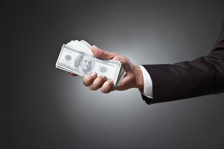 businessman hand holding money on dark background photo