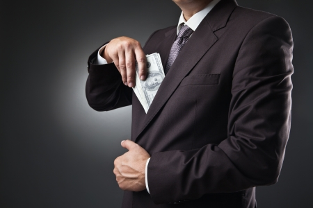 putting money in pocket: businessman in suit putting money in his pocket on dark background
