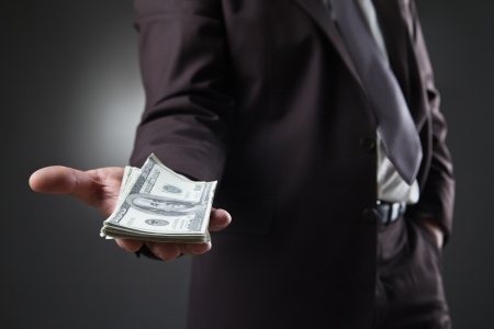 businessman in suit holding money on dark background