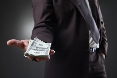 zakenman in pak aanhouden van geld op een donkere achtergrond