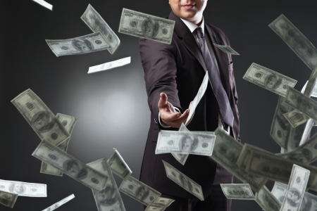 money flying: Handsome young man throwing money over dark background Stock Photo