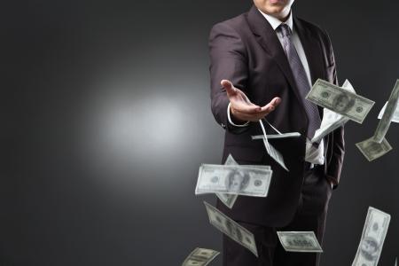 dinero volando: Apuesto joven tirando el dinero sobre fondo oscuro
