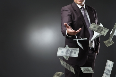 earn money: Handsome young man throwing money over dark background Stock Photo