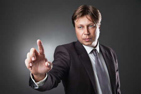 Businessman pressing an imaginary button on bokeh over dark background photo