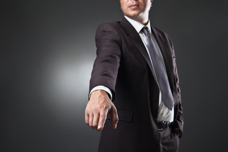 commanding: Portrait Of Young Man Points A Finger over dark background. Commanding Stock Photo