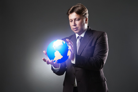 Hand of Business Man Hold Earth Globe on dark background photo