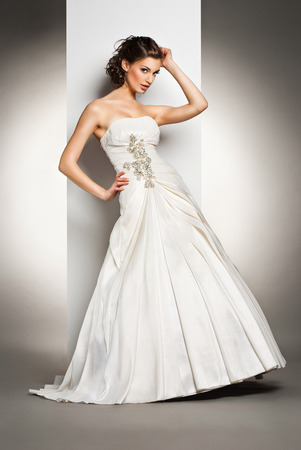The beautiful young woman posing in a wedding dress over grey backround