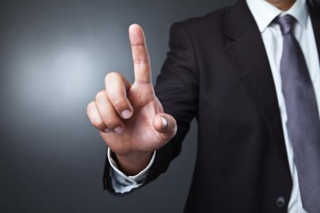 Hombre de negocios que presiona un botón imaginario en bokeh sobre fondo oscuro Foto de archivo - 22761086